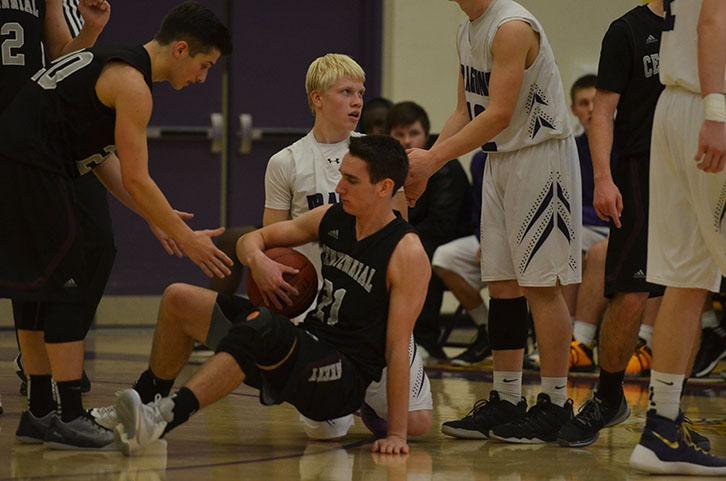 During the second half of the game senior Erik Francios gets up from the ground after falling alongside the Ankeny Centennial player. Our basketball teams took on the Ankeny Centennial Jaguars at home Jan. 5 the boys lost 67-43 and the girls won 61-41.
