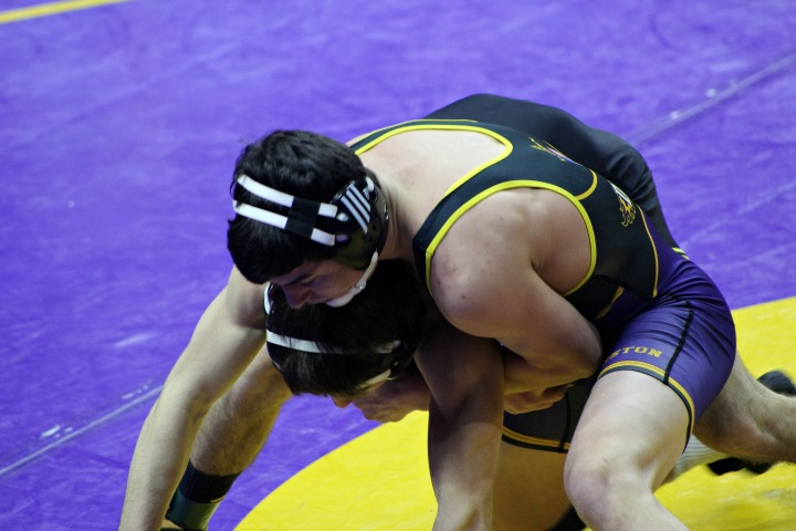During the state wrestling meet Feb. 17, senior Ethan Ksiazek attempts to bring down his opponent from S.E.Polk. Ksiazek competed during state individuals with a sprained ankle and dislocated shoulder. Ksiazek still managed to place fourth in state finals for the 132 pound weight class.