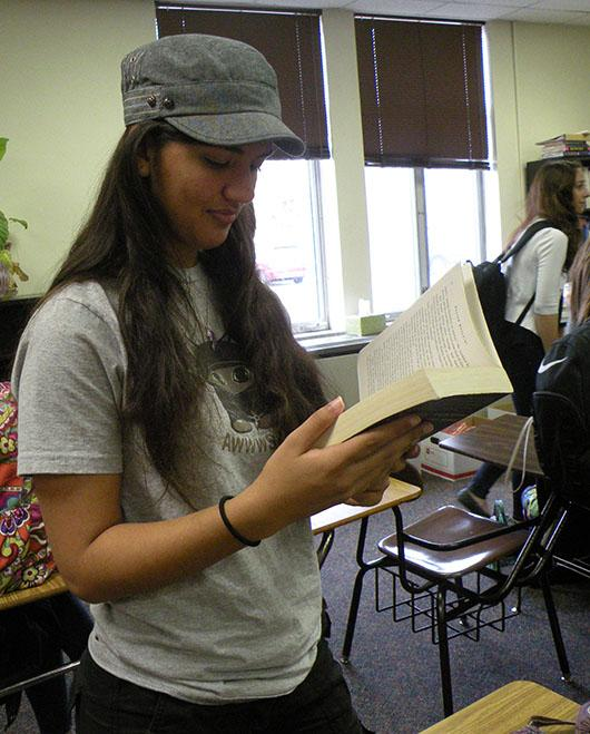 Sophomore Shabana Gupta reads a book for her English class. Gupta has worn a hat to school most days for the past two years.