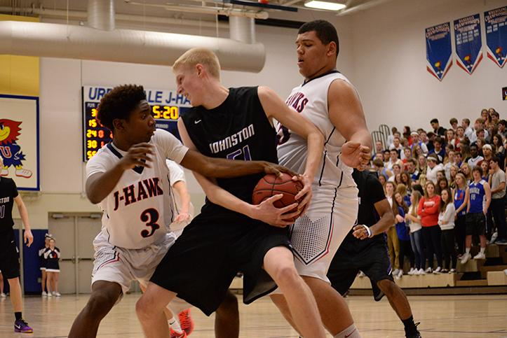 Senior Devin VanderWerrf fights for the ball against Urbandale opponents. The Dragons defeated the Jayhawks  Jan. 29th.