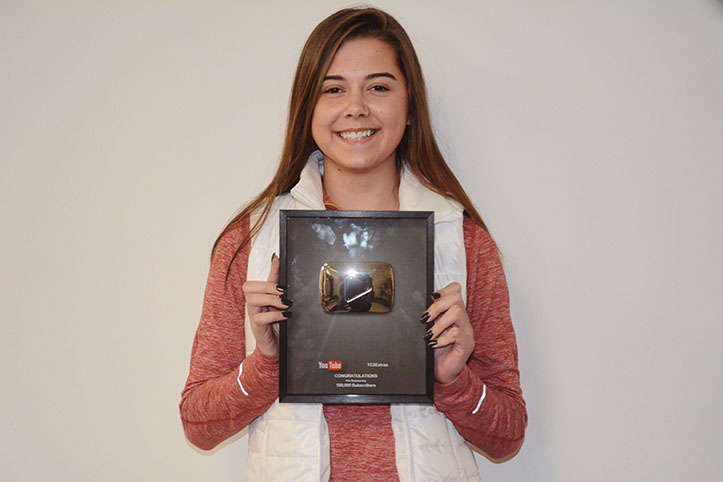 Sophomore Maggie Atchenson poses with her over 500,000 subscribers YouTube plaque. Atchenson and her two cousins started the cheer channel together.