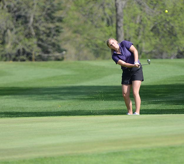 Senior Kennedy Kramer chips the ball on to the putting green on the second hole. Kramers nine-hole average score is 51.50.