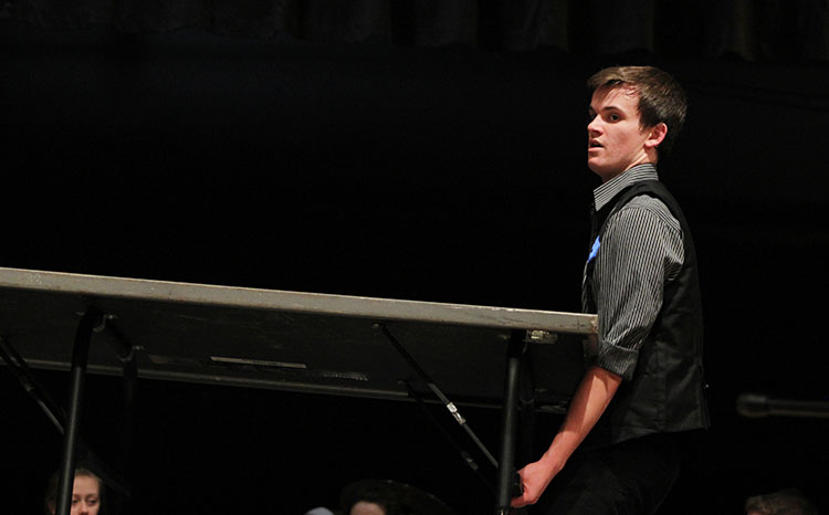 Senior Carter Spugin waits to carry a riser off stage during the rehearsal. Innovation will be performing at Fame, a competition that could send them to show choir nationals, Saturday, April 9.