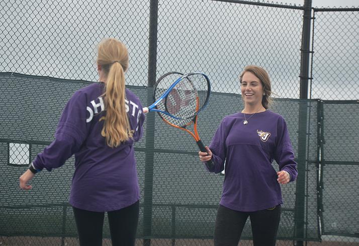 After senior Kathryn Paszkiewicz scores a point, senior Megan Crotts gives her teammate a high five with her racket. The players also received yellow flowers and sand castle buckets full of goodies.