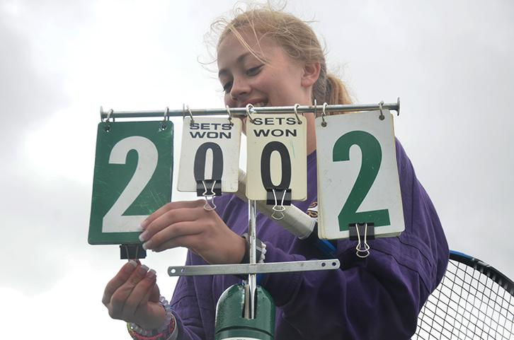 Senior Kathryn Paszkiewicz changes the numbers on the ---. Paszkiewicz played doubles with fellow senior Megan Crotts against a SE Polk opponent.