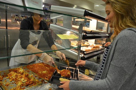 Senior Lizzy Salmon serves  lasagna to senior Lizzy Orr as part of her Culinary 3 assignment. The Culinary 3 class provided lasagna, tiramisu and chocolate cake as a lunch option April 8.