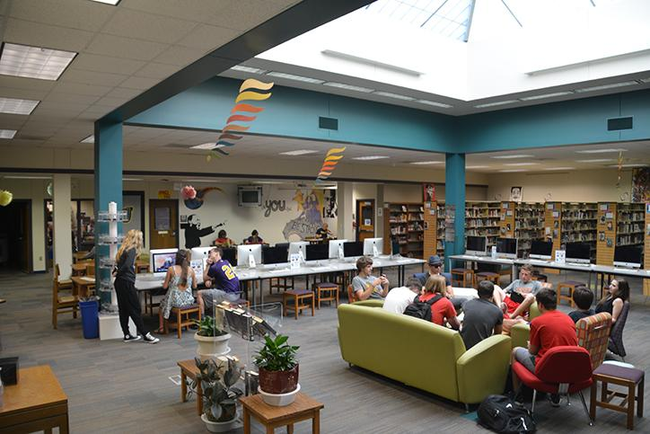 Students converse during third period in the library while others work on the computer. In order to be in the library if in study hall, students need a library pass that can be picked up at the beginning of the day.