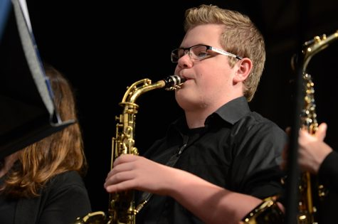 Playing on the alto saxaphone junior Charles Charlie Hoekstra focuses during the prime of their final song. Both Concert and Wind Symphony band had their last concert on May 16 at the middle school.
