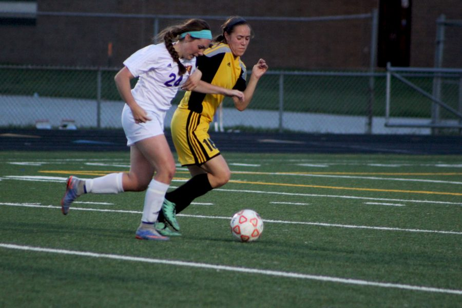 Senior Sam Birmingham tries to keep possession of the ball against S.E. Polk. The girls' varsity team is 13-4 with their last loss coming to Waukee May 24.