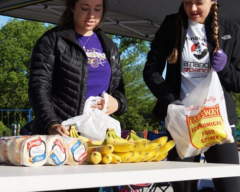 Prepping for potentially hungry participants juniors Sophie Catus and Madison Mehls set out bananas and other foods. Participants were free to pick up snacks and water bottles after completion of the race.