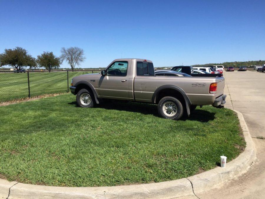 A student parks their car on the grass after no spots were left in the tennis court parking lot. Senior Alec Wray captured the moment and posted the photo on Twitter.