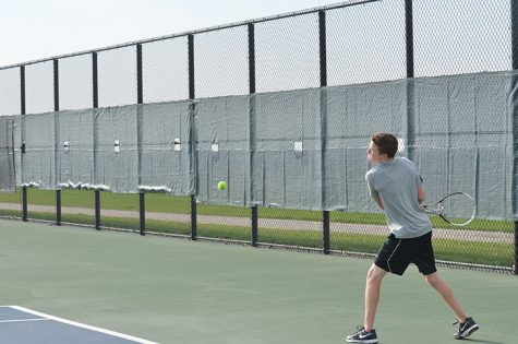 Prepping to hit the tennis ball senior Joel Heil plays against an Ankeny Centennial opponent. The Dragons ended up losing Ankeny Centennial 4-7.