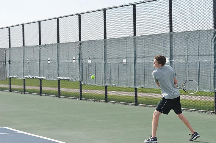Prepping+to+hit+the+tennis+ball+senior+Joel+Heil+plays+against+an+Ankeny+Centennial+opponent.+The+Dragons+ended+up+losing+Ankeny+Centennial+4-7.