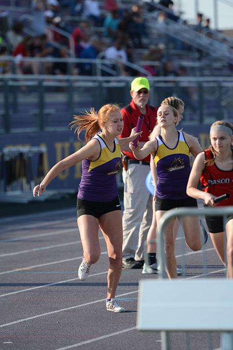 Freshman Macy Thompson hands off the baton to senior Anna Toot in the Distance Medley. Toot placed 18 in the 800 M run at the state meet with a time of 2:23.30.