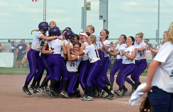 The girls' varsity softball team rushes together moments after winning the game. This was their second state win in four consecutive trips to the state finals.