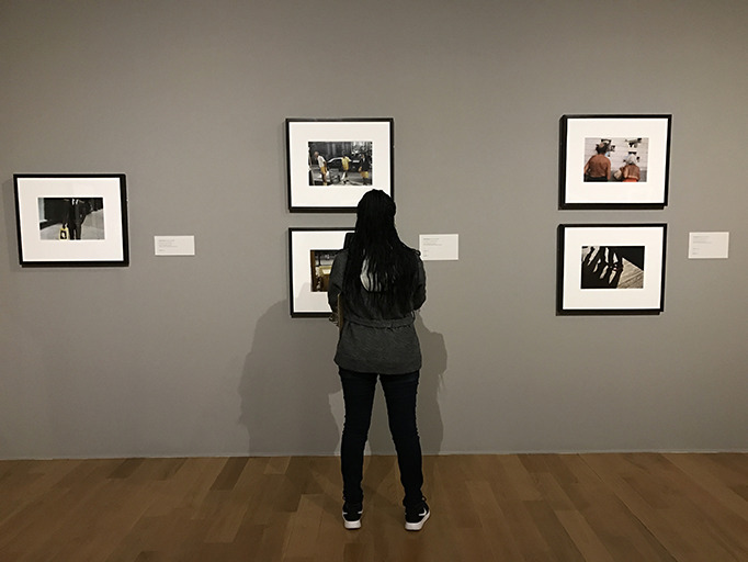 A student stands before a wall of Vivian Maier photos. Students in art classes had the opportunity to see the exhibit Nov. 15 on a field trip.