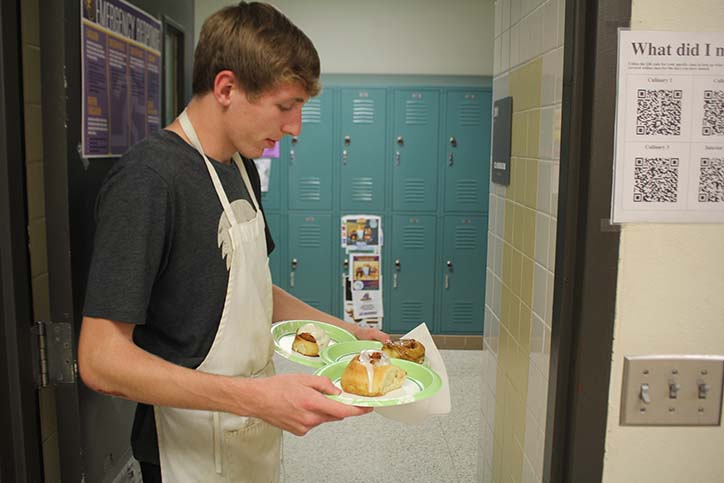 Jordan Goreth '17 takes hand-made cinnamon rolls to various teachers during cinnamon roll event in culinary class.