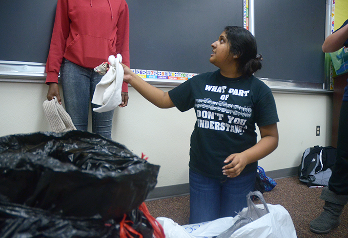 Parul+Srivastava+%2719+helps+sort+and+count+donations+into+plastic+bags.+Classes+who+donated+the+most+items+received+breakfast+pizza.