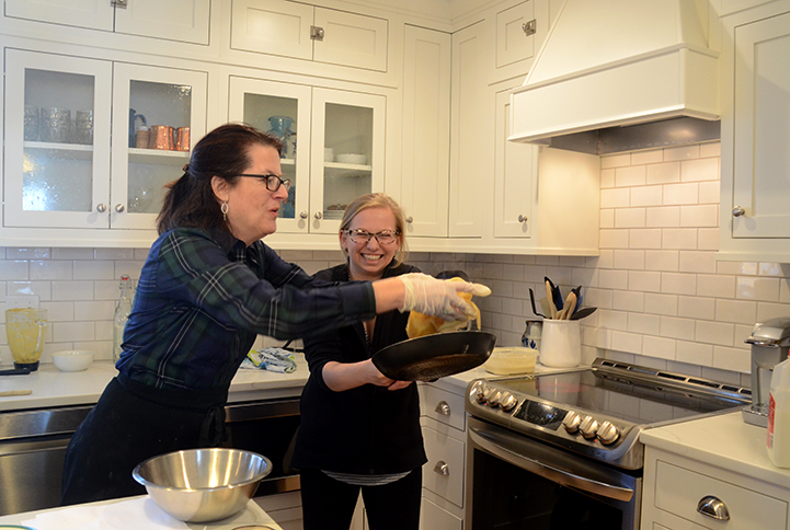 Chef Wini Moranville helps Bryony Whitelaw '17 flip a crêpe, barely missing the pan. AP French students took a field trip Dec. 13 to enjoy French food and culture.