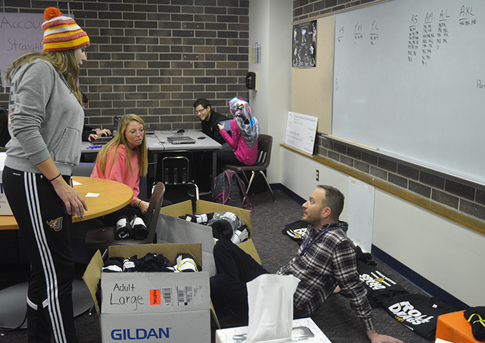 "Stefanie Stanisic '17 and Madison Nanke '17 assist teacher Tim Brickley in the organization of the ""Roll Drags"" shirts the entrepreneurship class Dec. 13. The shirts will be handed out in time for the Johnston versus Urbandale basketball game Dec.16."