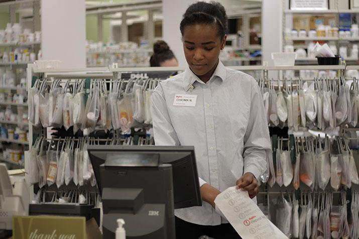 Chioma Nwizu '17 prepares a prescription for a customer. She interns at the Johnston HyVee pharmacy.