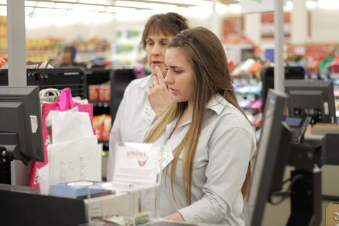Adina Blazevic '18 assists a fellow employee in correcting a customer's receipt. She was put in charge of supervising the cashiers at the Johnston HyVee.