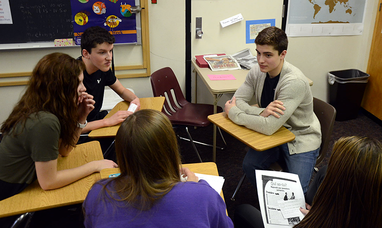 William Croteau speaks with a small group of French 4 students. Three hockey players from Quebec spoke to the class.