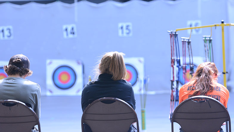 Henry Fisher 17 and Taylor Eidson 18 sit next to an opponent while looking towards the targets. The archery team ranked 13 out of 23 teams.