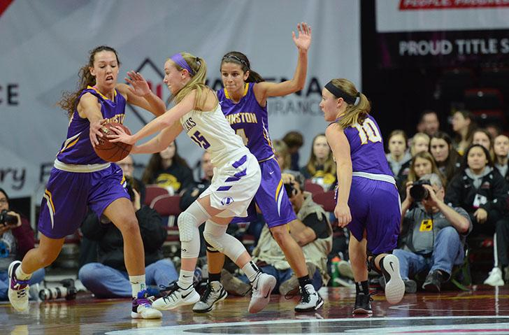 Attempting to get the ball from her Indianola opponent, Taryn Knuth '17 reaches her hand out while her teammates step back. The girls lost the quarterfinal round of state basketball against Indianola, 77-67.