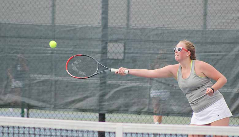 Eileen Mooran '17 reaches to hit the ball back towards her Urbandale opponent Macy Havran. Johnston won the tennis meet 6-5.