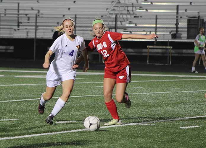 Macy Thompson '18 runs in front of Dallas Center-Grimes opponent  Alexa Smith to kick the ball. The girls won the game against DC-G 6-0.