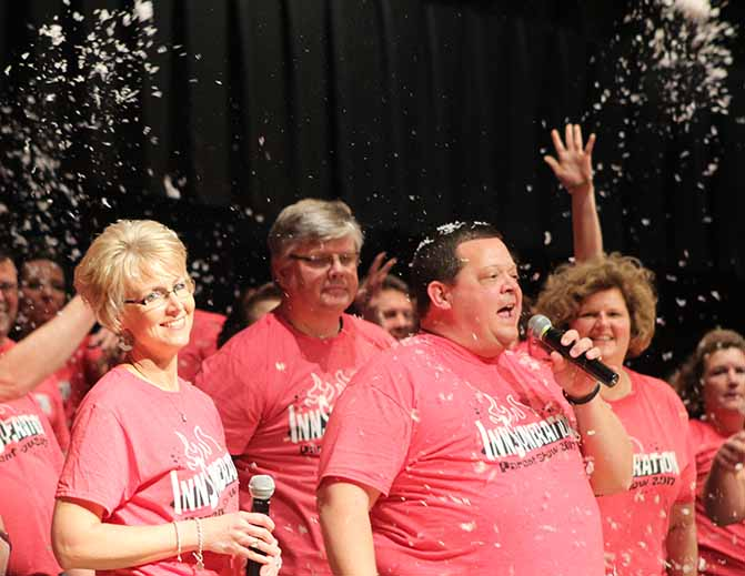 Parents Julie and Jeff Lorenz, parents of Ben and Brady Lorenz 17, sing a duet as others throw fake snow into the air. During the last show choir performance parents of show choir students performed a show of their own reflecting their thoughts on the season, including the cancellation of the trip to Hastings, MN due to the weather.