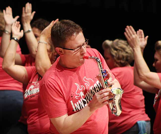 Chris Burgess, father of Kyle Burgess 17, plays a toy saxophone during the parent performance. … mimicked his son's role in Innovation's show as a saxophonist.