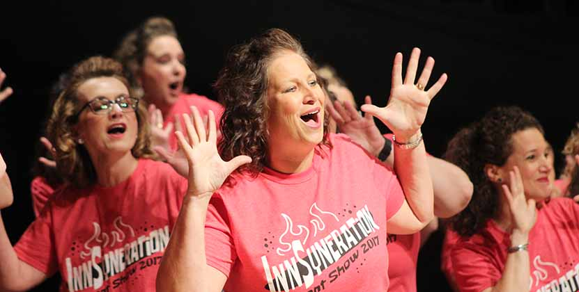 Michelle Roquet, mother of Ellie Roquet 17, poses with jazz hands during the parent show. During the last show choir performance parents of show choir students performed a show of their own reflecting their thoughts on the season.
