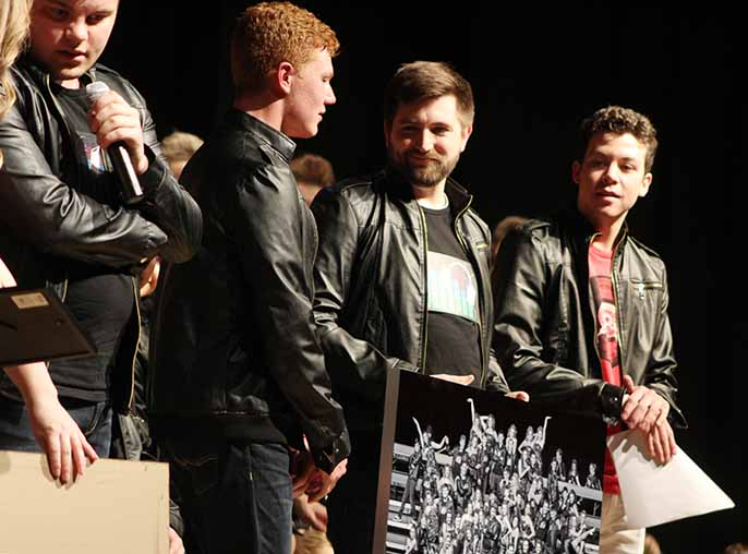 At the conclusion of the the show choir performances Colin Pranger hands Johnathan Edgeton a photo of Innovation as a gift. Edgeton is the seventh grade vocal music and show choir director and helps Innovation prepare for competitions.
