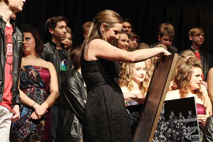 With Innovation standing behind her, director Hannah Ryan looks at a framed poster she received as a second gift from the seniors in Innovation. Seniors decided to all sign a poster to give to Ryan as a gift. Ryan moved from the middle school to the high school with the current graduating class back between the 2013-14 and 2014-15 school year.