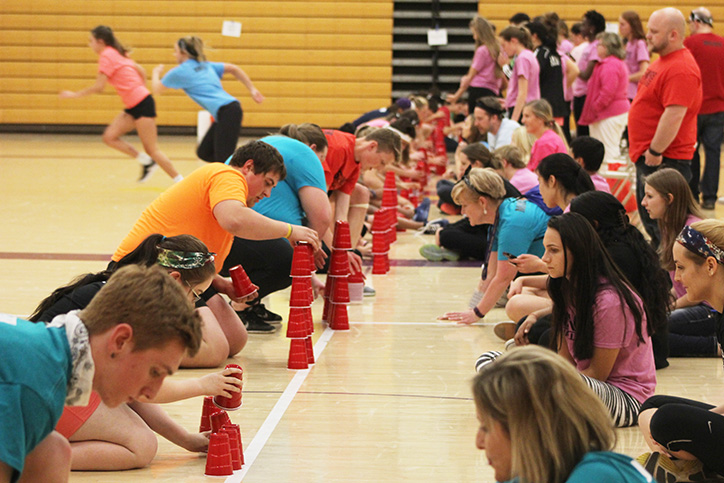 Seniors from different teams line up to stack cups while their advisors and judges watch. For the event each member of a team was required to stack 15 cups in a five, four, three, two, one order then unstack them.