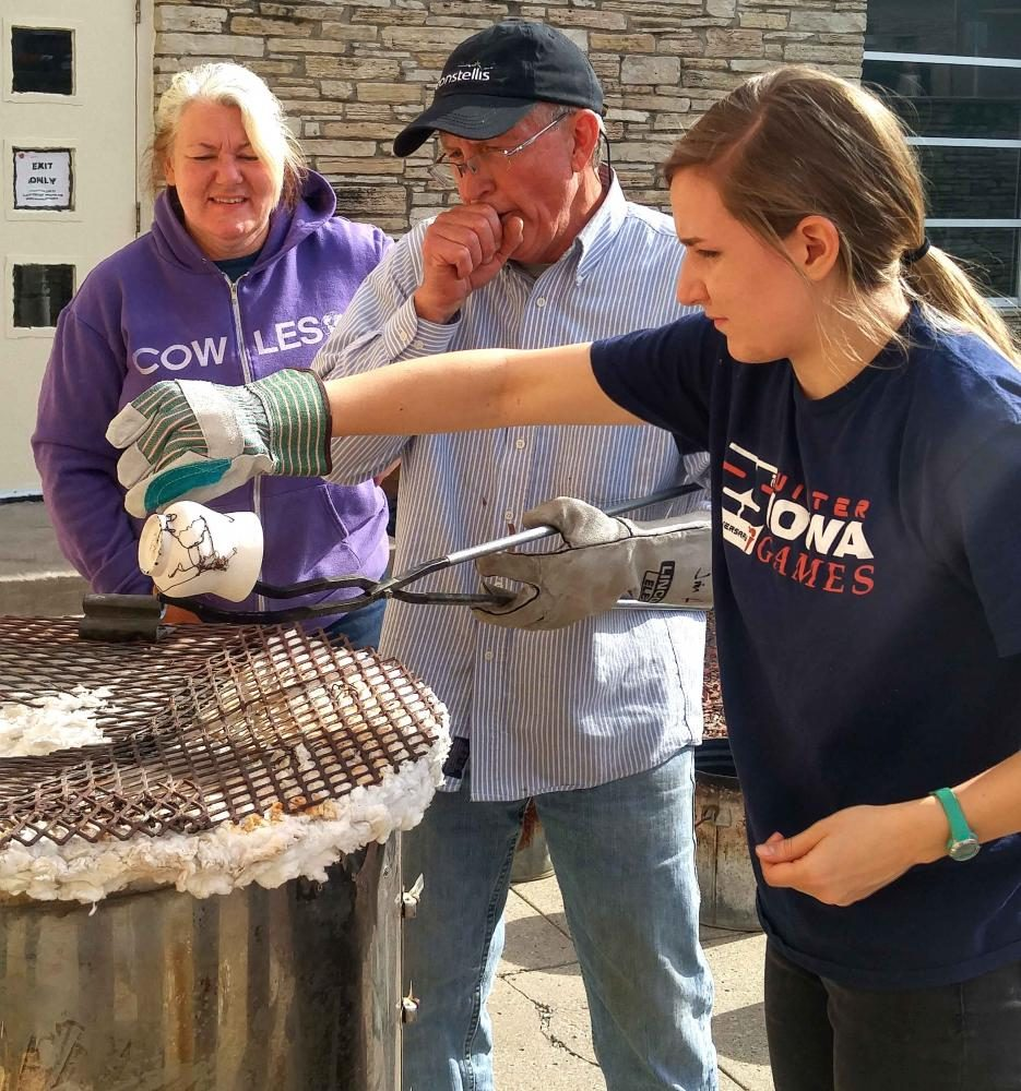 Sarah Nelson '18 is placing horse hair onto her pot as Jim Hubbartt holds it above the kiln's opening. Many of the hair pieces shrivaled and fell off, into the hole before they could leave a mark on the pot's surface.