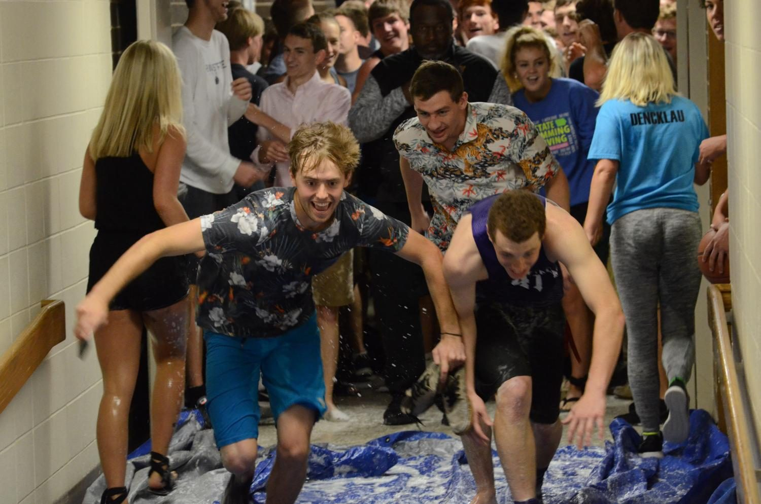 [Left to right] Nate Blanchard '17, Drew Decker '17 and Jack Dreyer '17 slide down together. Seniors used water bottles and soap to make the tarp slippery as their senior prank May 25.