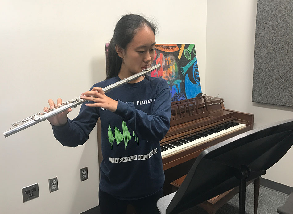 Anna Xiang '18 plays the flute in one of the spare band practice rooms.