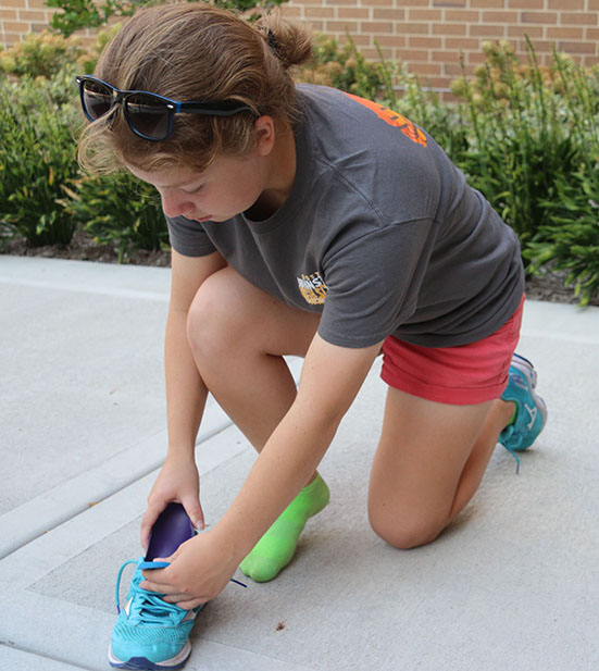 Julie Srail '18  inserts her plastic foot brace so she is able to run without pain.