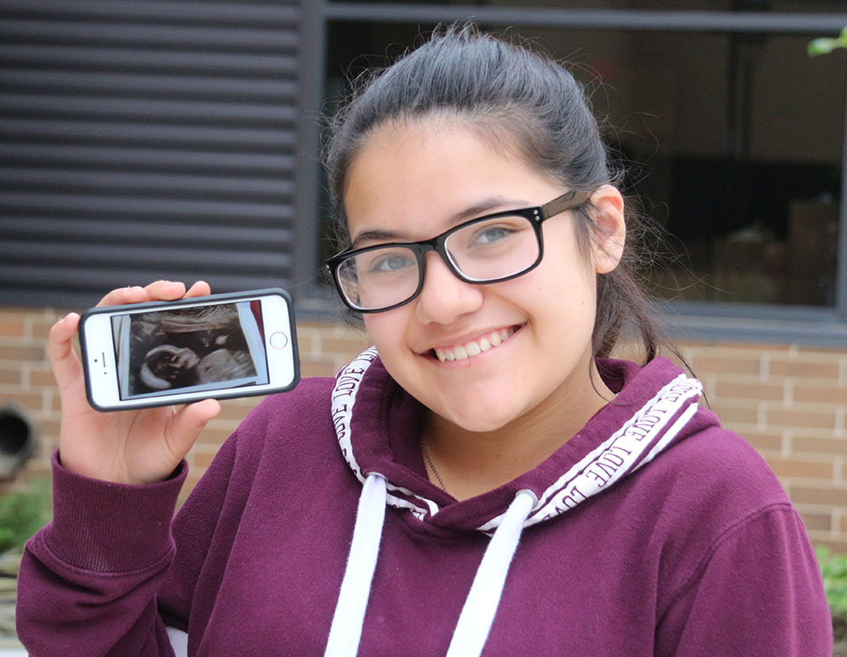 Karla Lopez '19 holds up the ultrasound picture of her baby sister due in December.