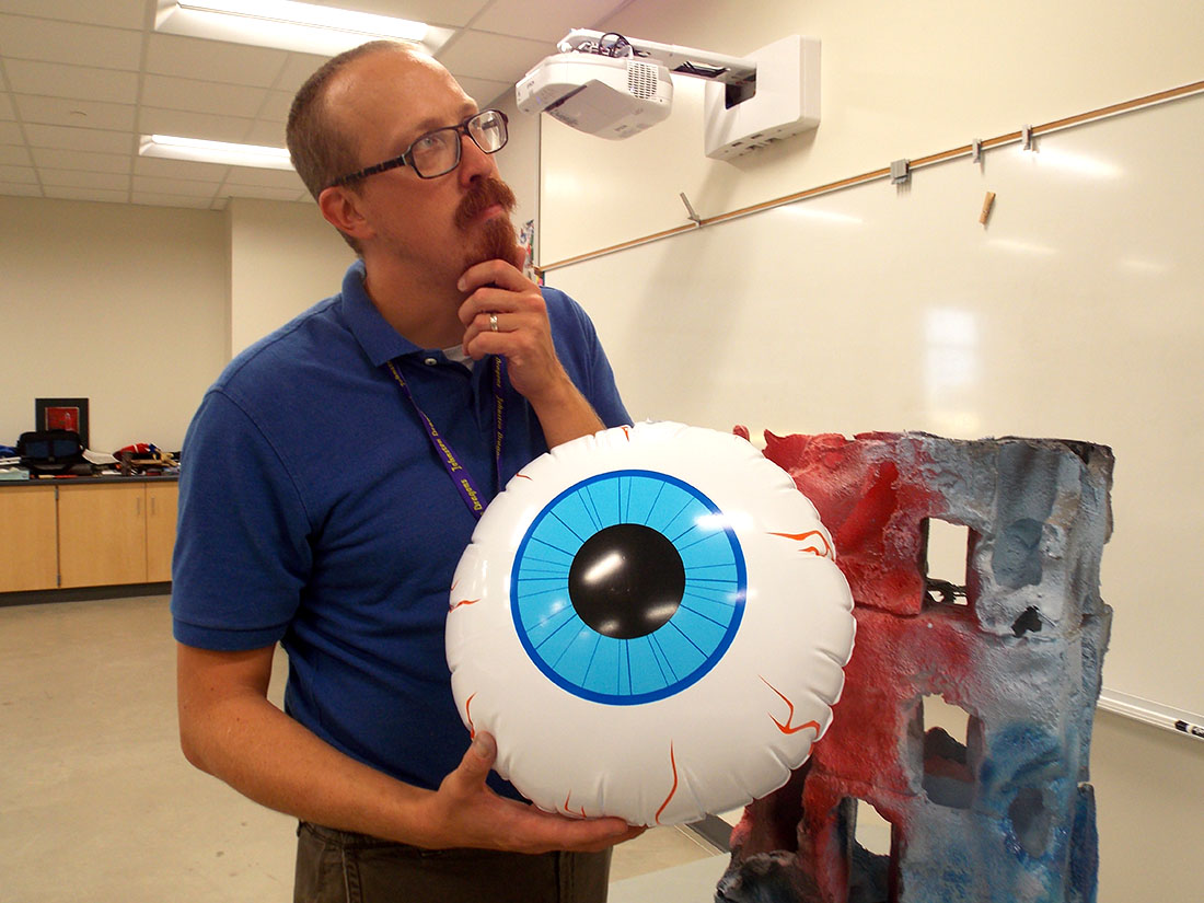 Andrew McCormick hold up one of the props he keeps in his classroom. He firmly believes that people should not take themselves too seriously.