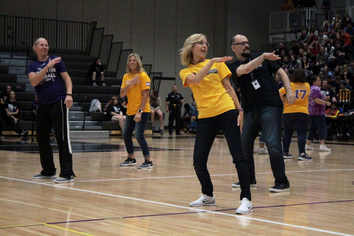 Julie Probst, Ed Walker and Destiny Willer dance to Juju on that Beat at the assembly. The teachers participated in the annual staff dance at the homecoming assembly.