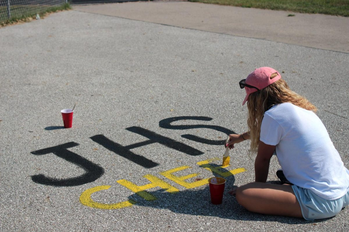 Kali Kramer '18 paints the cheer stadium painting. Kramer helped created three other groups' paintings.
