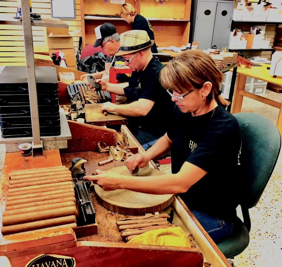 Cuban women roll cigars in a local Miami shop on Calle Ocho.