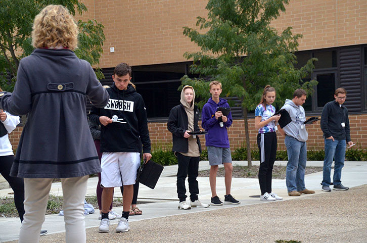 Lisa Horsch instructs students for the next round of their lab. Biology students were tasked to collect beans with different utensils from the ground to represent survival of the fittest.