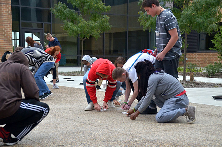 Students hunt for beans on the ground in one of the courtyards. Students recorded the amount of beans they had collected after the trial.