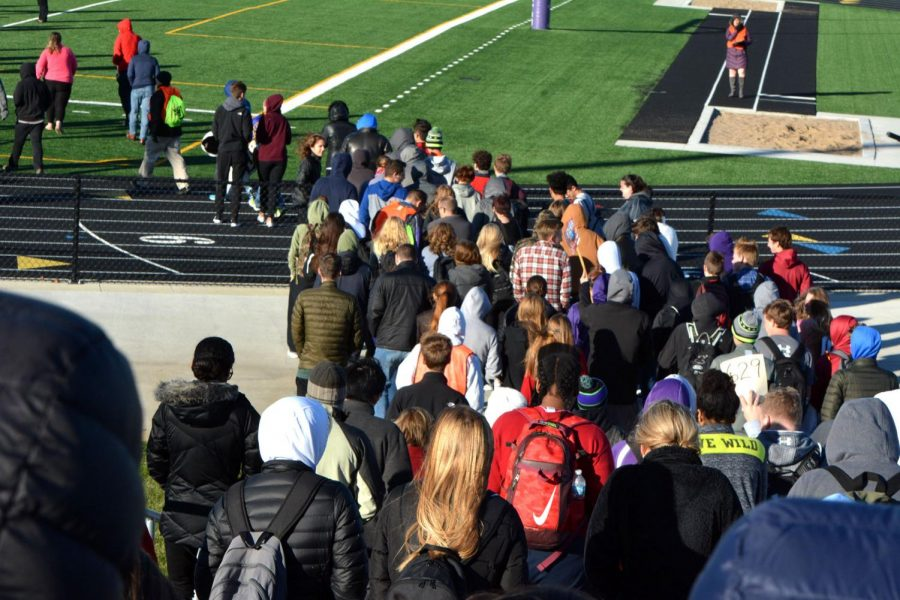 Students prepare to reunify on the football field. Reunification points are determined by the students' teacher at the time of the alarm.