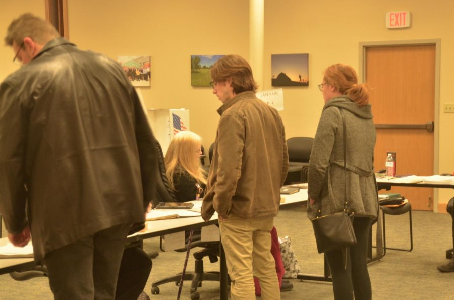 Voters check in with volunteers to confirm their registration to receive their ballot.